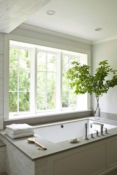 Gorgeous master bathroom with blue paint color and wood paneled drop-in tub