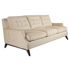 Tufted sofa with angled feet. Made in the USA.   Product: SofaConstruction Material: Oak, plywood, polyester and foam