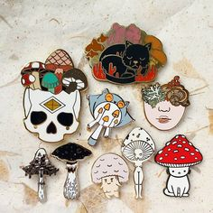 All my mushrooms (I think) . . . [Image description: 9 enamel pins arranged on cream paper the pins are a skull and mushrooms by @triangleofbears a cat and mushrooms by @breebird33 a flying squirrel by @fukuroguro a girls face with mushrooms by @yaspaints a by @northernspells a starry mushroom by @wideeyeddesigns a short mushroom girl by @alumandink a tall mushroom girl by @gildedcreaturesart and a mushroom cat by @ponypeople ] . . . #enamelpins #lapelpins #pingame #pinstagram #enamelpin…
