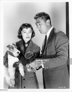 Phyllis Kirk holding Asta the pup, as Peter Lawford magnifies spot on gun for her in a scene from the television series 'The Thin Man', 1957.