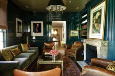 The library's peacock lacquered walls and ceiling were hand-painted by Barry A. Martin Painting Contractors. The 1948 Finn Juhl chairs in walnut and new saddle leather belonged to the husband's parents in New Orleans. The distressed vintage leather club chairs were restored by Marcelena Racatune of Larru Leathers. The Barn Owls is an original John James Audubon painting purchased at a Louisiana plantation estate sale. Photographs of Japanese fetish dolls by David Levinthal.