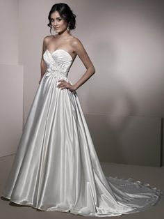 Style No. BE140    A traditional charmeuse ball gown embellished with beaded floral decor is paired with modern design feature with the addition of pockets located on both sizes to accommodate the modern bride, before completing with a semi-cathedral train.