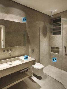 """15. Espelho iluminado. Ele parece solto, mas está fixado 7 cm à frente da parede. A iluminação (lâmpada fluorescente T5 com reator) vem de trás – efeito que valoriza a textura irregular e rústica do cimento. 16. Tudo de cimento. A bancada, a cuba e a prateleira inferior repetem a matéria-prima de todo o apartamento – o cimento queimado. O concreto armado moldado na obra evitou custos excessivos. """"Fazemos as fôrmas de madeira e preenchemos com essa massa. Depois de seca, tiramos o molde e a…"""
