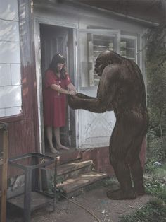 "Photographic recreation of Janice Carter Coy pulling out hair from the hand of a sasquatch named Fox when giving him some garlic. She claims to have grown up with a family of sasquatches and that they speak English. She also co-authored a book with Mary Green called ""50 Years With Bigfoot""."