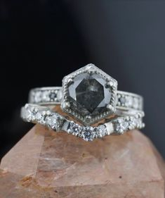 This rough diamond hexagon ring invokes the look of a meteorite space rock using a natural raw gray black diamond. A hidden Wonder Woman logo sits under the ring head, a secret message to the bride-to-be. This rough diamond hexagon ring was designed and named for an Abby Sparks Jewelry client. #roughdiamondengagementring #weddingringset #diamondweddingband #uniqueweddingring #custommadejewelry #denverjewelry