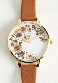 You'll be happy to give the time to passersby with this beautiful Olivia Burton watch on your wrist! A caramel leather band and a gold frame is joined by jewel-toned flowers and butterflies atop a white backdrop, providing you with a timepiece of pure enc