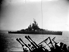 As seen from the HMS Enterprise (D-52), the Nevada (BB-36) is moving into position off Cherbourg to bombard enemy gun batteries on 25 June 1944.