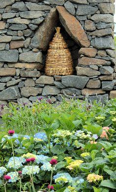 Bee skep displayed in a stone wall!!! Bebe'!!! Love this bee skep!!!