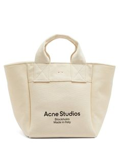 Acne Studios - Elevate your off-duty rotation with Acne Studios' Alisse ivory tote bag, crafted from thick canvas that brings a sculptural finish to the silhouette. It's made in Italy, as shown by the striking black logo print and opens through a red leather-tied top into a roomy compartment set with a zipped pocket. Carry it by the top handles to tap the season's business-casual mood. Canvas Tote Bags, Canvas Totes, Black Tote Bag, Cloth Bags, Luxury Bags, Acne Studios, Red Leather, Reusable Tote Bags, Purses