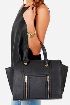 """If we had to choose one bag to rescue a wardrobe in need, the Wing-Woman Black Handbag would be on the top of our list! A chic winged style, constructed from pebbled vegan leather, takes center stage with shiny gold hardware, black piping and two exterior zip pockets. Unzip this gold-footed purse to reveal a roomy interior with black fabric lining, as well as three interior pockets. Twin tote handles have a 6.5"""" drop. Buckled shoulder strap measures 47"""" at longest adjustment."""
