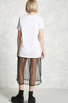 "A knit T-shirt dress featuring a ""No Shade"" center front graphic, a sheer mesh skirt, a boxy fit, cuffed short sleeves and a ribbed round neck."