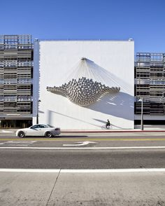 Commissioned by the City of Santa Monica, Cradle is situated on the exterior wall of a parking structure at a shopping mall – originally designed by Frank Gehry. The whole array reflects distorted images of passersby. Distorted Images, Graffiti, Environmental Graphics, Environmental Design, Expositions, Outdoor Art, World Trade Center, Public Art, Installation Art