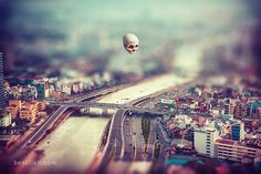 """Godseye"" - surreal floating skull above Ho Chi Minh City (Saigon) in Vietnam, by Joseph Westrupp, bestilled.com. The cityscape looks miniaturized due to tilt shift effect. Click the image to buy a giclee print (options include frames, canvases, metal prints, and more)."