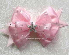"A Luxurious Pink Satin and White Sheer Ribbon Bow with a Gorgeous Sparkly Rhinestone Center. #282  Measures 4-3/8"" across or 3 1/8 for Toddler Size. $18  PERFECT FOR: Your Disney Aurora Costume, Weddings, Parties, Performances and other Beautiful Occasions! See our other Princess and Disney Character Bows: Elsa, Anna, Rapunzel, Ariel, Cinderella, Maleficent, Belle, Snow White and Minnie Mouse.  ITEM DETAILS: All bows are heat sealed to prevent fraying. All products come from a smoke..."