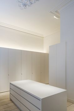 Minimalist storage room. Cabinets for supplies, vendor  books, etc. Island storage for  fabrics and custom materials. Above cabinet lighting for controlled and architectural lighting source.  — Hans Verstuyft Architecten