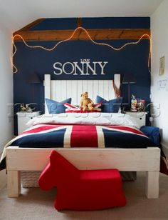 Boys bedroom with Union Jack bedlinen and blue painted wall with Love Sonny in white lettering above