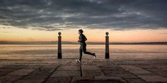 Photograph of a man running along a pier during sunset, with a harbour in the background