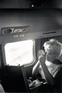 FRESHENING HER MAKEUP - Marilyn Monroe applies makeup after a meal on board a commercial airliner.