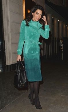Amal Clooney wears a suede ombré trench coat with tights, pumps, and a leather satchel