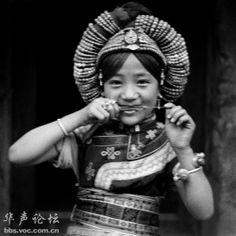 """1934年摄街四川理番 阿坝理番藏族,讲""""嘉戎""""话。这个嘉戎贵族少女,以红珊瑚珠盘成头饰,身穿花衣,腰缠花带,耳带珊瑚银环,为当时贵族盛行的 一种装束。图中少女正在吹口弦,奏时用线扯动竹簧,发声清越为竹制口琴也。"""