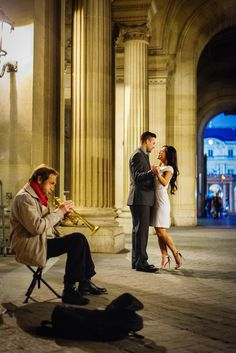 Beautiful couple dancing in front of a trumpet player in one of the passages from Louvre Museum in Paris.  Picture captured by Fran Boloni, Paris engagement photographer