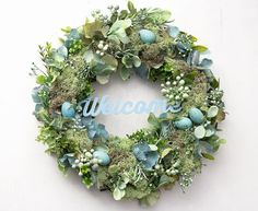 This beautiful wreath is perfect for display throughout the Easter and the spring season. It is made of moss, great mix of faux greenery, speckled eggs and decorated with wooden Welcome sign or rabbit. Due to the handmade nature of this wreath, it may vary slightly from the image - this is all part of its unique charm.  Two sizes are available for this wreath: 12/ 30.5cm or 14/ 35.5cm. Please choose your size at checkout.  The biggest version of this wreath is available here, 16.5: ...