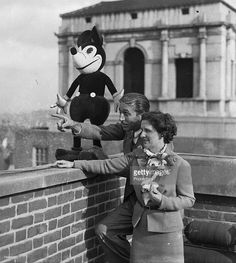 Cartoons and Animation, 12th June 1935, Famous American animator Walt Disney and his wife with cartoon character Mickey Mouse on the roof of their London Hotel