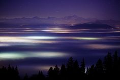 Lights of towns and villages in the clouds in the area of Lake Geneva. The Mont Blanc massif can be seen in the background. - Svetlá miest a dedín v oblakoch v oblasti Ženevského jazera. V pozadí vidno masív Mont Blancu.
