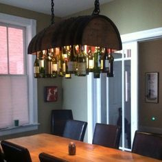 Wine rack from barrel . but aren't wine bottles supposed to be horizontal? I'd like this as a lighting fixture in a bar area. Wine Bottle Chandelier, Diy Chandelier, Bottle Lights, Barrel Projects, Diy Projects, Wine Barrel Furniture, Pool Table Lighting, Kitchen Lighting, Wine Rack