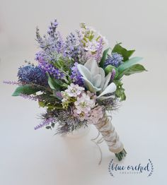This silk wildflower bouquet has lilac, lavender, wildflowers, and lambs ear. Wrapped in burlap and lace with a twine overlay, this makes a beautiful, rustic wedding bouquet! This rustic bouquet is about 10 inches wide and 12 inches tall. Flower selection and color, as well as stem wrap selection and color, can be customized upon request. We offer cream lace, natural burlap, burlap & lace, or any color(s) satin. If you have something different in mind, just send us a message. We love cus...