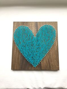 "Aqua Blue Heart String Art - 12"" x 12"" - Nail and White String Art - Handmade - Ready to Ship - Ready to Hang with Hardware - Home Decor - Wall Art. This beautiful string art is made by me in my home. I start by milling the wood, sanding, then staining the wood. Once dried, I pick a pattern, pound the nails in and tie the string to make this amazing artwork. The popular wood is stained in dark walnut and measures approximately 12"" wide by 12"" tall by 2"" deep. This artwork is made in a…"