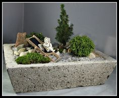 Simple miniature garden design - conifers, trough, sun chair and rocks strewn