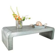 Coffee table with aluminum panels and studded accents.  Product: Coffee tableConstruction Material: Wood and aluminumColor: SilverDimensions: 16 H x 60 W x 24 D