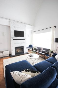 This gorgeous Modern Living Room reveal is finally here! This space came a long way from an outdated, empty space in this beautiful barn home. Love all of the contemporary DIY and decor ideas in this beautiful living space! The tiled fireplace and blue couch are stunning! Such a huge transformation. Floor to ceiling fireplace and white painted vaulted ceilings are gorgeous! #bluecouch #livingroom #renovation #diy #blackandwhite #nordic #minimal #modern
