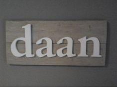 Wit houten letters op vergrijsd steigerhout.