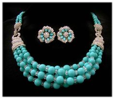 Transform into a Cinderella at the ball with this, a superb Marcel Boucher simulated turquoise and diamond bib necklace and earrings.  The necklace is fetching, with multi-strands of vivid turquoise beads accentuated by a pair of huge faux diamond rhinestone bands. The earrings are equally stunning, with a combination of turquoise cabochons and rhinestones. Circa the 1950s-1960s.