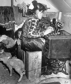 Loomis Dean, Lillie Begay sitting on an empty explosive box and working with the new sewing machine, her son and a lamb beside her, USA, May 1951.