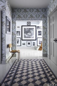 Encaustic tiles are inset into wood planks to form a geometric print floor in the pale blue entry hall of the a Bedford, New York home. The vintage-inspired, light blue patterned wallpaper is by Schumacher, and a photo wall collage of black and white photography makes a statement in the next room.