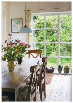 An airy dining room full of rustic charm and spring freshness.  I love the chairs, table, and of course the peonies!
