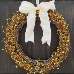 This primitive autumn wreath features yellow and orange pip berry garland, securely attached to a grapevine wreath base, and would make a lovely Halloween or fall door decoration. Your wreath will be handmade to order, and finished off with a bow in your choice of color.