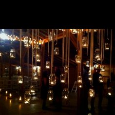 Very neat barn wedding idea. Mason jars with candles hanging behind the alter.