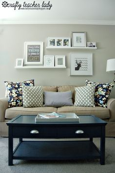 Love the shelves and frame arrangement as well as the couch and cushions, although those cushions are too symmetrical..
