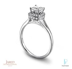 Jared® platinum and diamond engagement ring with round diamonds that frame the center.
