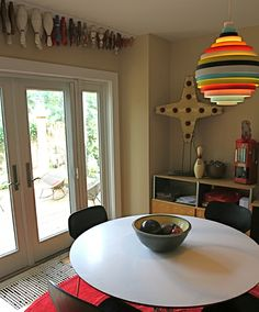 In order to create more space to display our client's various collections we designed a deck with to visually open up the small dining room. A vintage bowling pin collection now hangs upside down over the French Doors.