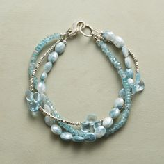 ICE STORM BRACELET -- Sterling silver beads glisten among the cool hues of blue zircon, topaz and mystic sapphire in this bracelet. Three strands
