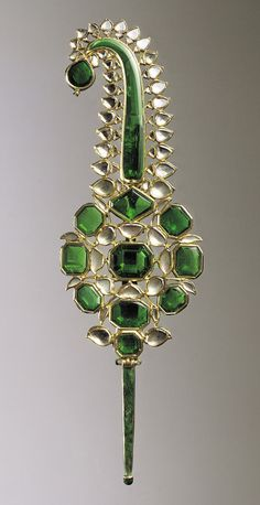 Gold turban ornament worked in kundan technique and set with emeralds and diamonds, the reverse with champlevé and overpainted enamel North India or Deccan, 2nd half 11th century AH/2nd half 17th century CE 17.4 cm high; 5.25 cm wide