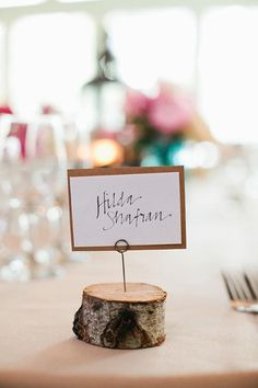 Use a small drill bit to make a hole in a cut log, then insert a wire card holder | Brides.com
