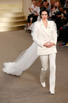 Here she comes! The teen model covered up her lean and slender frame in a structured off-white satin suit, from the fashion house's latest collection, which included a tailored jacket with dramatic broad shoulders and slim-fit trousers