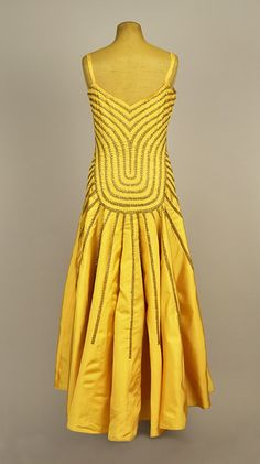 "LANVIN COUTURE SEQUINED SILK DRESS, WINTER 1929 - 1930 Gold faille having sleeveless bodice with bands of tulle decorated with silver sequins and yellow prong-set rhinestones following the V-neck and U-shaped waistline, tulle neck insert, narrow strap, full skirt with inset bands in a sunburst effect, the hem dipping slightly in the back. Label ""Jeanne Lanvin Paris"" stamped ""Hiver 1929-1930"" inked on the back ""28.649"". B-38, W-30, L 51-54."