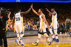 Stephen Curry and Draymond Green of the Golden State Warriors high five each other during the game against the Utah Jazz during Game One of the...